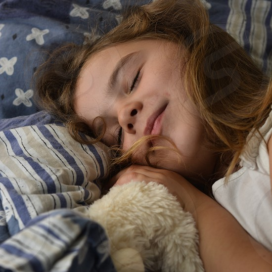 girl in white shirt lying on bed photo