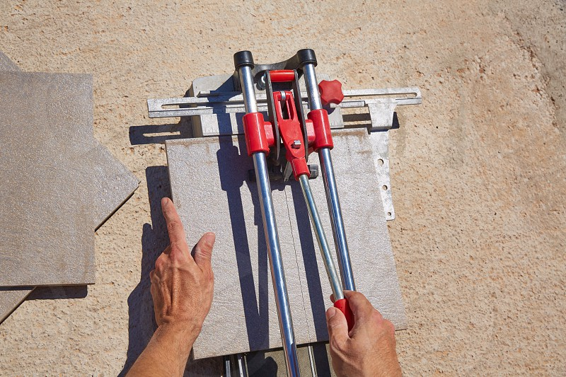 tile cutter machine with mason hands cutting tiles photo