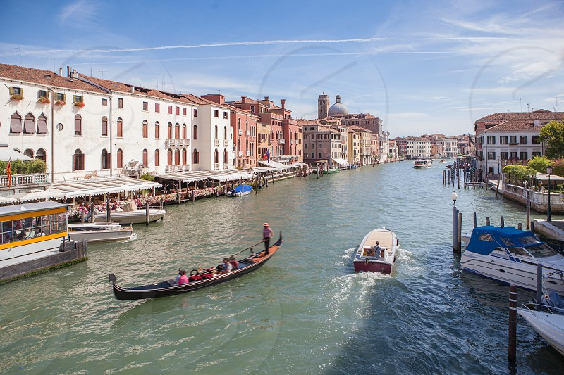 View of Grand Canal with gondolas and colorful facades of old medieval buildings from Rialto Bridge in Venice Italy. photo