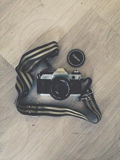 canon camera with black and gray stripe strap photo