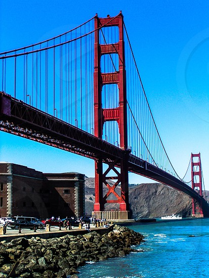 golden gate bridge with people bellow and white boat passing under blue and white sky during daytime photography photo