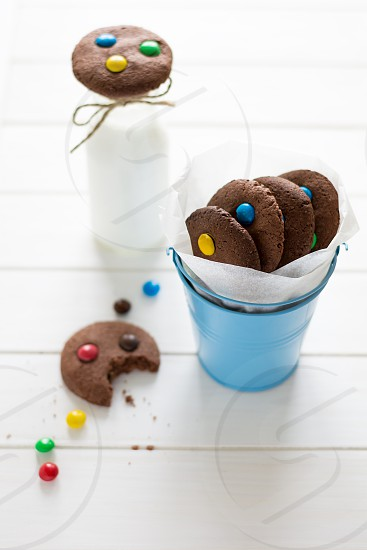 Homemade chocolate cookies decorated with colored candy drops and bottle of milk on white wooden background photo