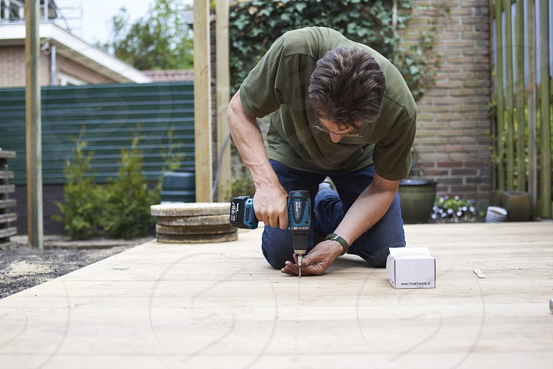 A handy man drilling and making a new outdoor patio sitting area in the back garden photo