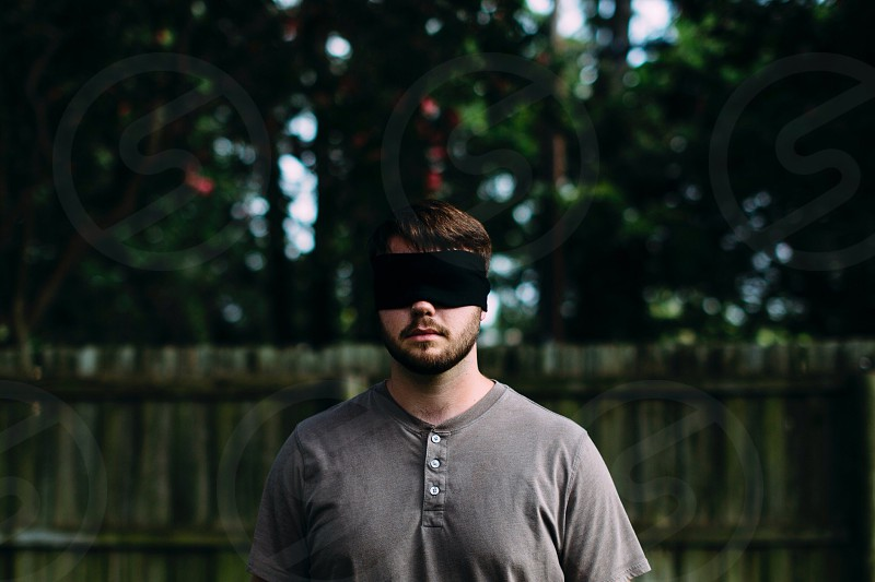 man in gray shirt with black blind fold photo