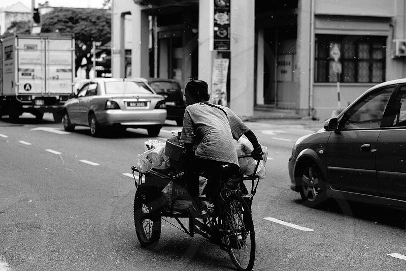 man riding a trike on road photo