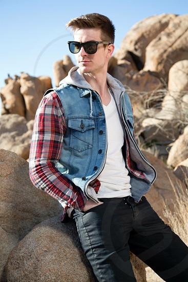 man in blue denim button up vest hoodie and red white plaid long sleeve shirt with white v neck shirt underneath and black denim pants with black wayfarer sunglasses photo