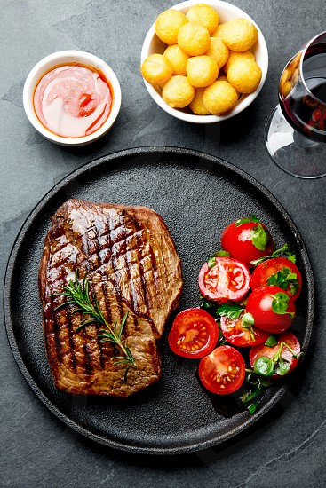 Grilled beef steak served on cast iron plate with tomato salad potatoes balls and red wine. Barbecue bbq meat beef tenderloin. Top view slate background. photo