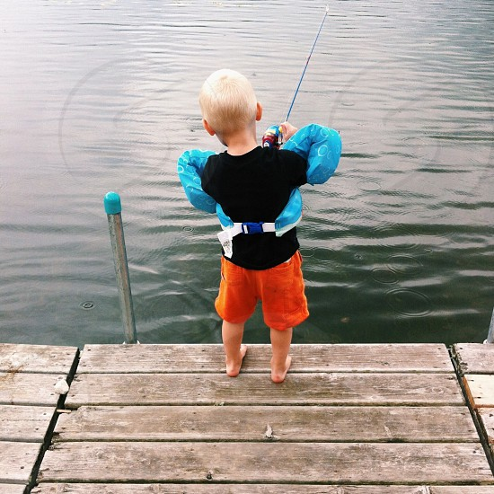 boy fishing on lake photo