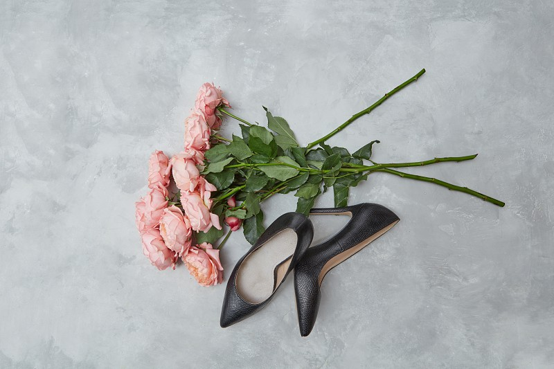 elegant black female shoes and a bouquet of pink roses on a gray background the concept of Valentine's Day photo