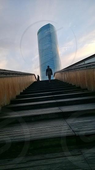 Solitary man walking towards Iberdrola tower in Bilbao. Building designed by Cesar Pelli photo