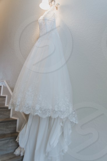 White wedding gown hanging on staircase wall photo