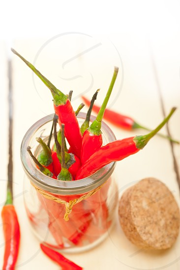 red chili peppers on a glass jar over white wood rustic table photo