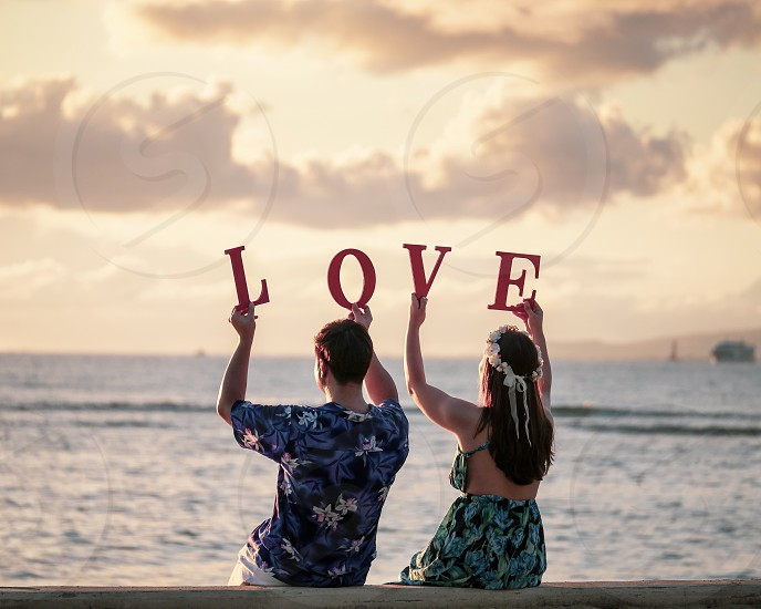 Honeymoon couple spelling the word Love with letters on the beach in Hawaii during sunset golden hour romance  photo