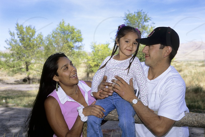 Happy Native American family portrait of a 4 year old daughter sitting on a farm fence with her mother and father. photo