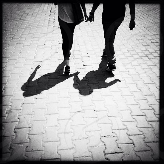 man and woman walking in the street photo