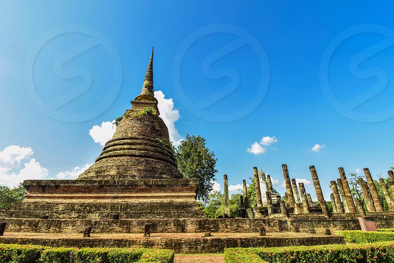Sukhothai Historical Park. In the past Sukhothai was Thailand's capital is thriving. The central government religion and economy within the national park is a landmark historic palaces places of worship with the city wall and moat surrounding the ancient city gates in a square. photo