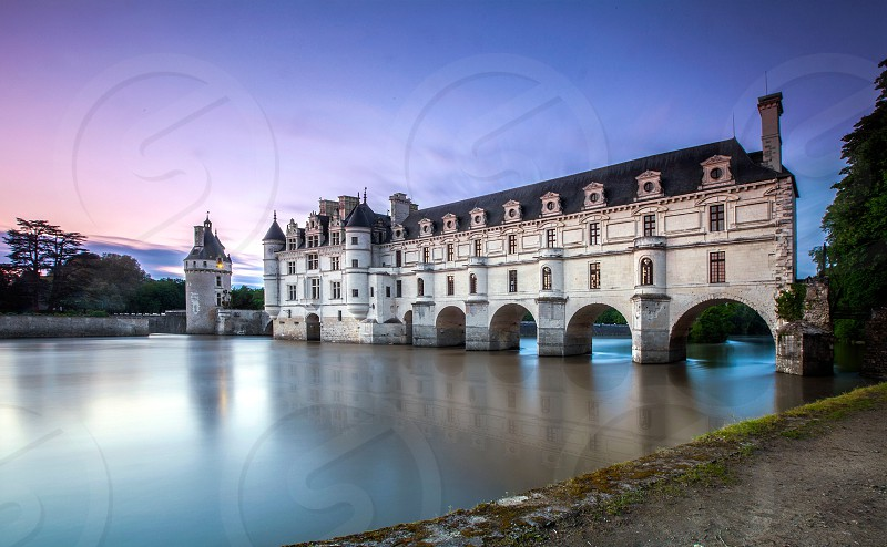 A bridge house in the Lior Valley France is reflected in the flowing waters that the bridge house castle sits above. photo