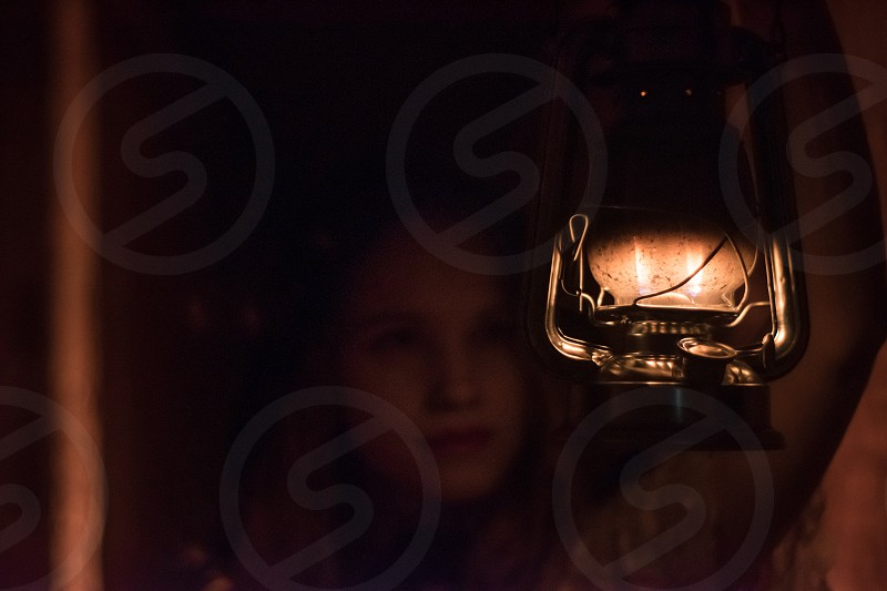 Portrait of young woman in vintage dress holding a vintage lantern in raised hand photo