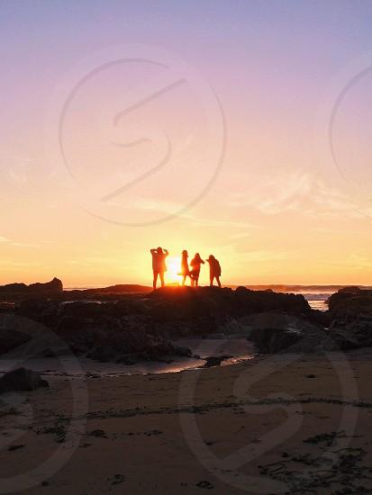 people standing on the seashore rocks photo