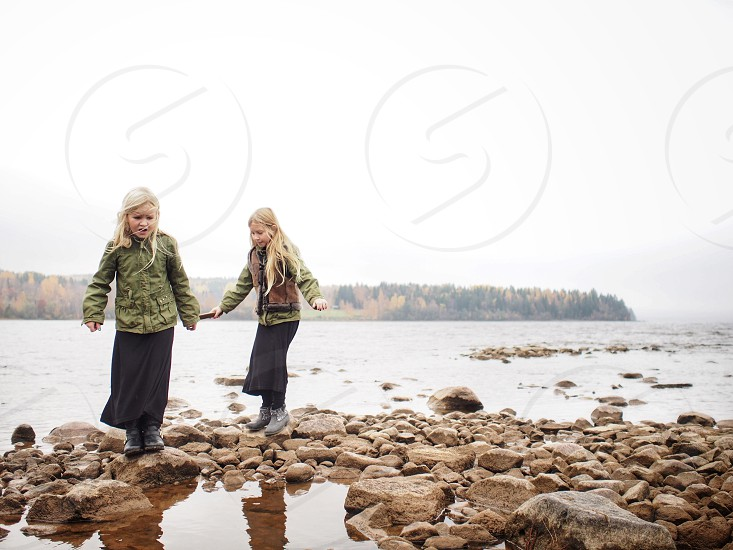 Girls sisters child kid jumping playing autumn fall lake water stone stones fun  photo