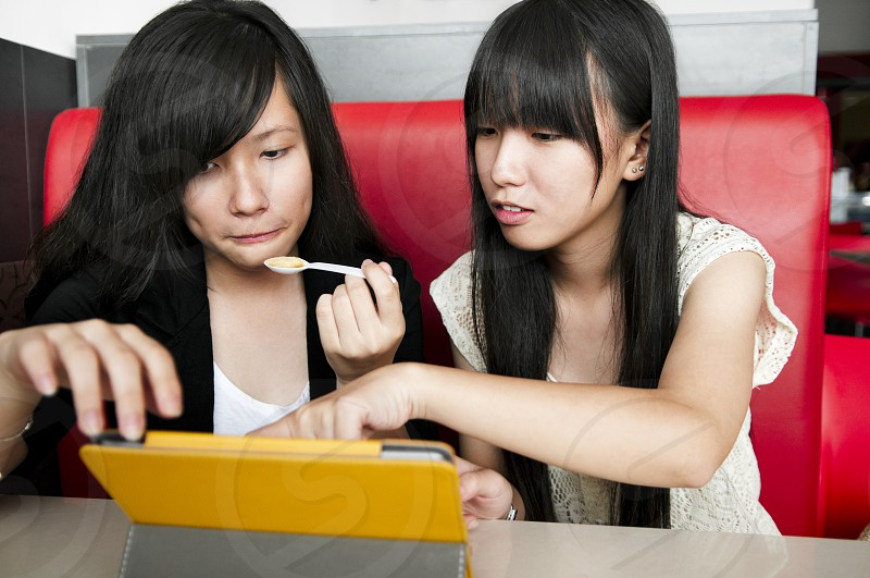 Teen girls viewing tablet computer in cafe. photo