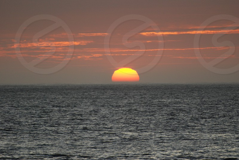 view of a sunset across the sea photo