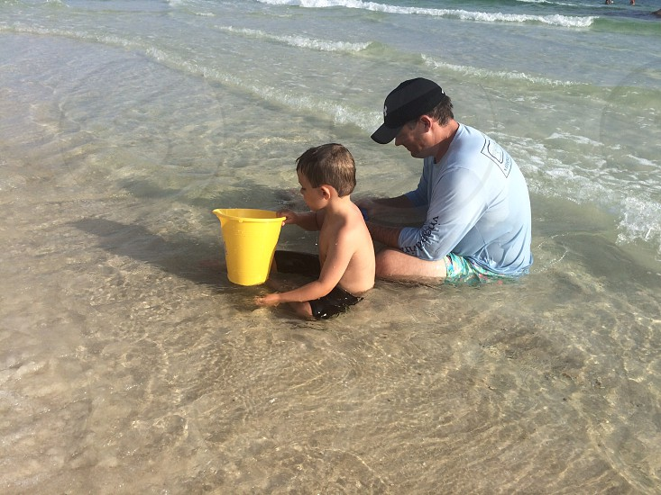 Dad playing in sand with his son collecting shells photo