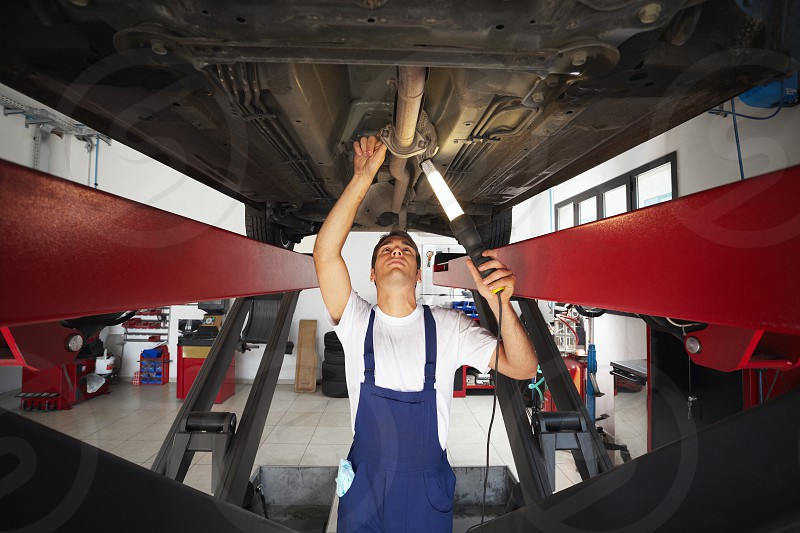 mechanic; man; car; working; repairing; engine; people; one person; male; Caucasian; young; adult; young man; mid adult; 30s; waist up; serious; concentration; overalls; front view; low angle view; standing; looking up; under; seeking; examining; holding; lamp; light; lighting; indoors; garage; transportation; transport; vehicle; auto; automobile; motor vehicle; broken car; repair; car repair; car part; auto repair shop; manual worker; fixing; mending; expertise; skill; work; copy space photo