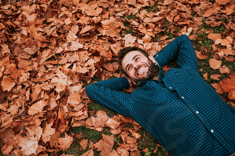 Young man lying down on the ground covered in autumn leaves photo