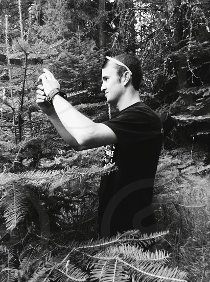 man in black t shirt taking picture photo