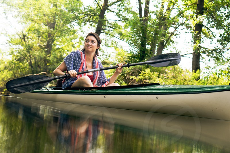 brunette woman with a double ended oar in a canoe on a river with green trees in the distance photo