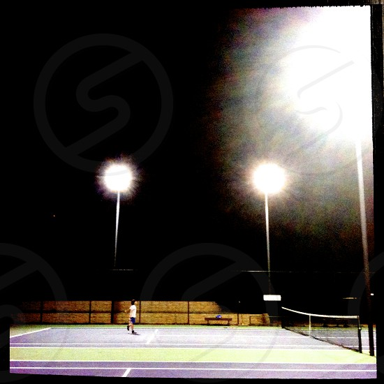 boy playing in the tennis courts at night photo