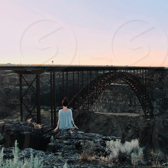 woman in teal long sleeved shirt sitting on edge of rock cliff facing brown steel railway bridge photo