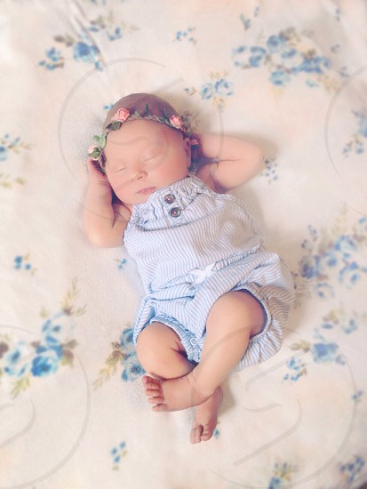 baby in blue jumper sleeping on bed photo
