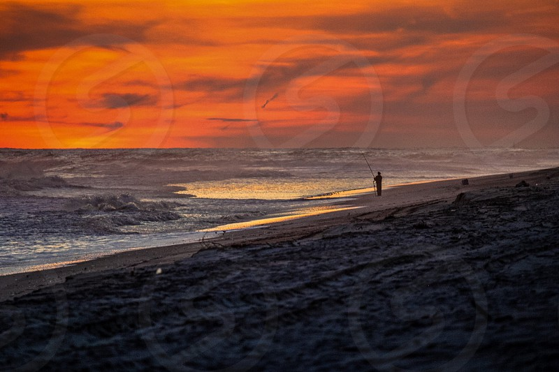 scenery of beach near gray sand under orange cloudy sky during sunset photo