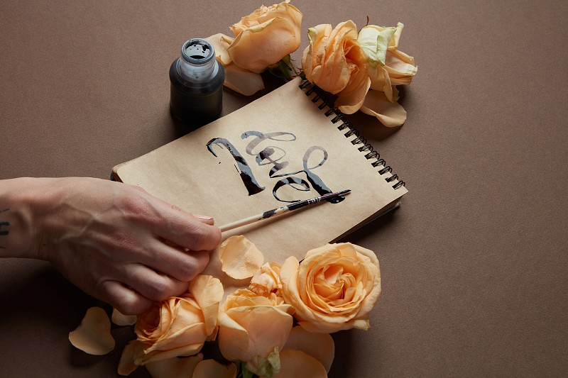girl writing the word Love in a notebook on a brown background with flowers. photo