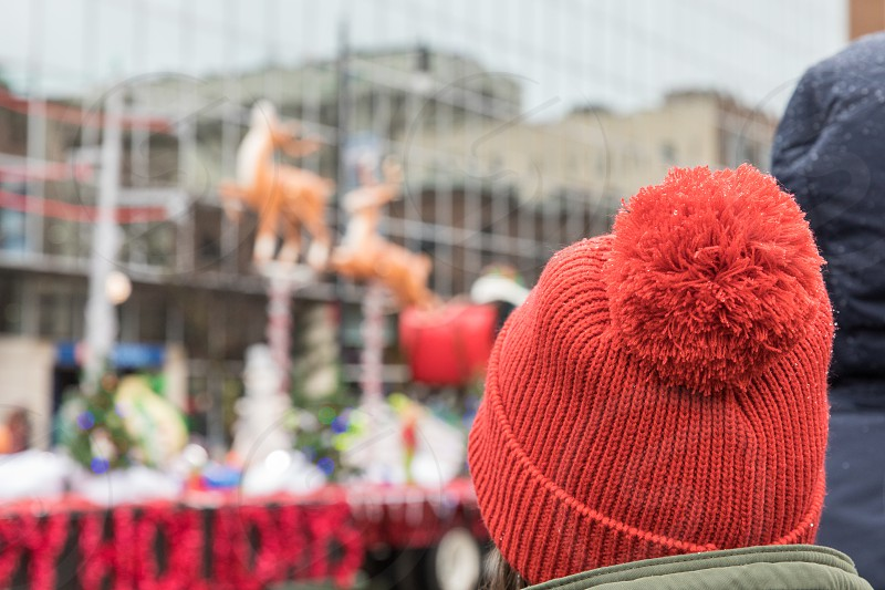 A woman wearing a pompom hat enjoying the Santa Christmas parade photo