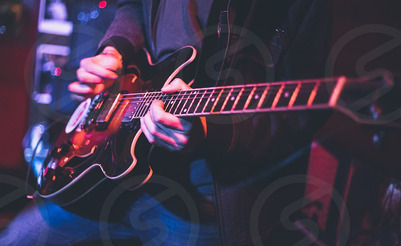 Electric guitar player on a stage with colorful blue and purple scenic illumination photo