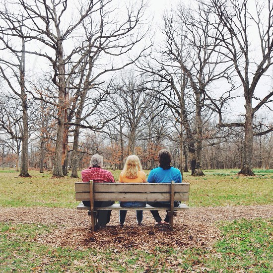 three people sitting on a wooden bench photo
