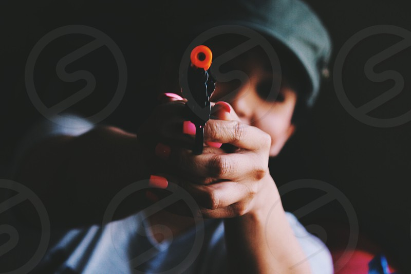 person holding a plastic toy gun photo