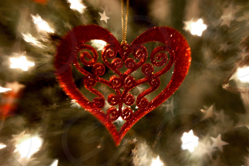 Red heart holiday ornament on a Christmas tree with star shaped bokeh photo
