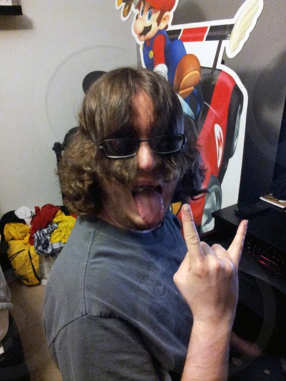 Young man making crazy face with hair in glasses and sticking tongue out. photo