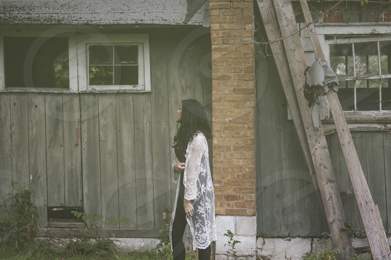 woman in white lace long cardigan and black leggings standing beside abandoned house photo