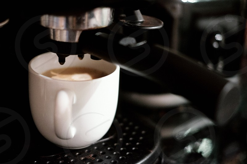 A fresh cup of coffee being made from a coffee machine photo
