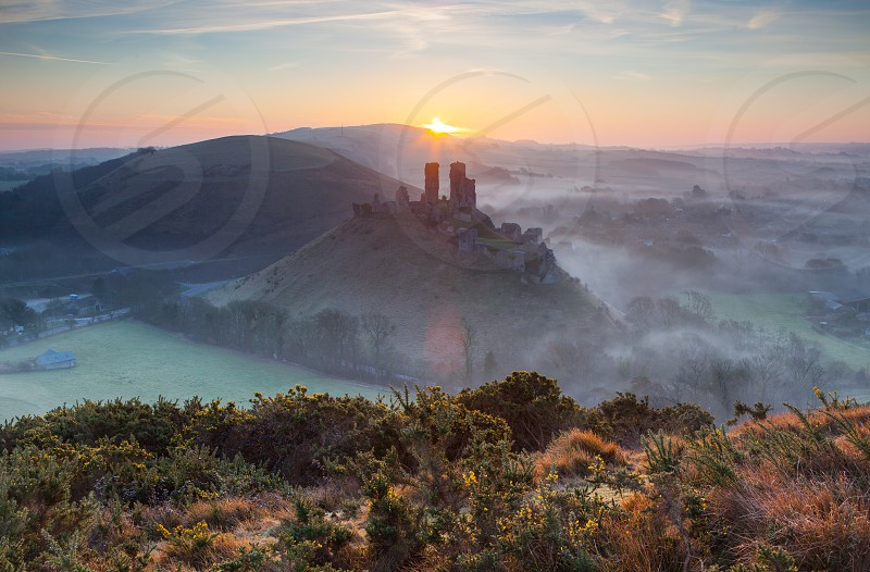Sunrise in the morning mist from a high view point at Corfe castle Dorset EnglandThe Square Wareham Dorset BH20 5EZ photo