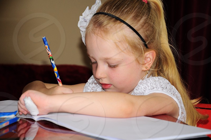 girl in white lace dress writing on notebook photo