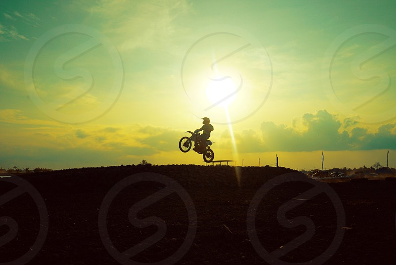 silhouette of a person riding a motocross dirt bike flying from ramp during day time photo