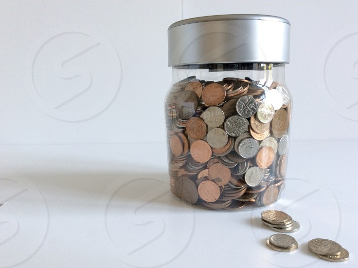 A jar of spare change sits against a white background photo
