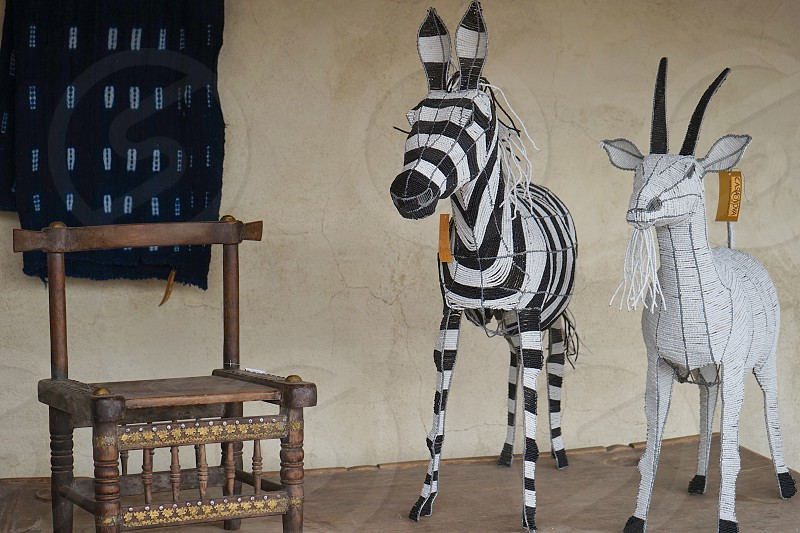 Wooden zebra and antelope models with chair and wall rug against stucco wall photo