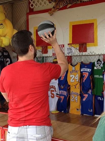 man wearing red t-shirt throwing basketball at hoop photo